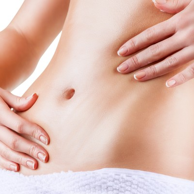 Close-up of a woman belly rubbed into the skin nourishing cream. Isolated on white background